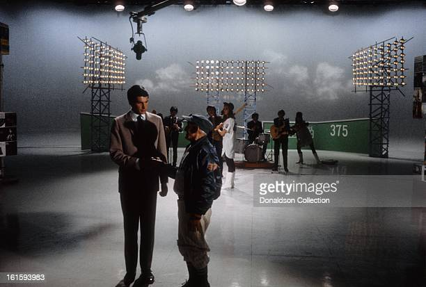 Actor and singer George Hamilton greets an impersonator of Mets manager Casey Stengel as they introduce Wayne Fontana and the Mindbenders performing...