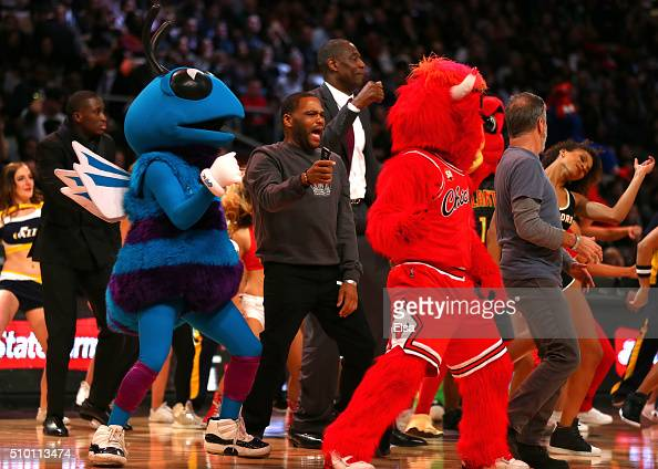 Actor Anthony Anderson former NBA player Dikembe Mutombo and TV personality Jon Stewart dance on court with mascots in the Foot Locker ThreePoint...