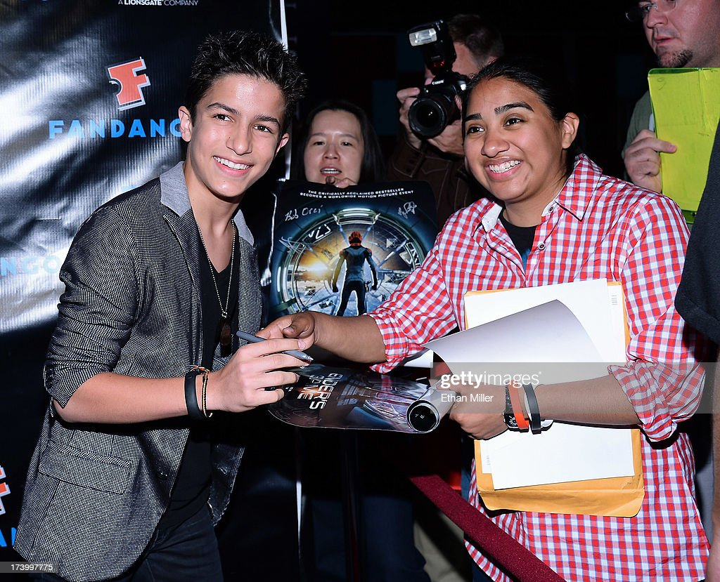 Actor Aramis Knight (L) signs autographs for fans as he arrives at Summit Entertainment's press event for the movies 'Ender's Game' and 'Divergent' at the Hard Rock Hotel San Diego on July 18, 2013 in San Diego, California.