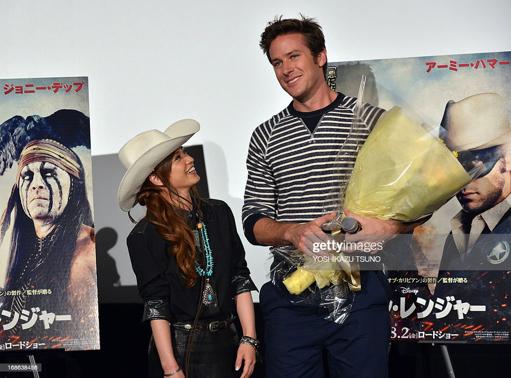 US actor Armie Hammer (R) smiles as he receives a bouquet from Japanese actress Airi Taira (L) upon his arrival at a press conference for his new film 'The Lone Ranger' in Tokyo on May 13, 2013. The movie, produced by Jerry Bruckheimer and co-starring Johnny Depp, will open in Japan on August 2. AFP PHOTO / Yoshikazu TSUNO