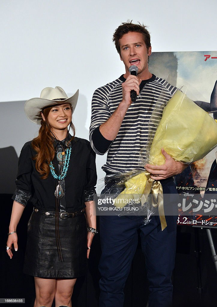 US actor Armie Hammer (R) speaks after receiving a bouquet from Japanese actress Airi Taira (L) at a press conference for his new film 'The Lone Ranger' in Tokyo on May 13, 2013. The movie, produced by Jerry Bruckheimer and co-starring Johnny Depp, will open in Japan on August 2. AFP PHOTO / Yoshikazu TSUNO