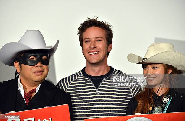 US actor Armie Hammer stands with Japanese actress Airi Taira and comedian Hiroyuki Amano at a press conference for his new film 'The Lone Ranger' in...
