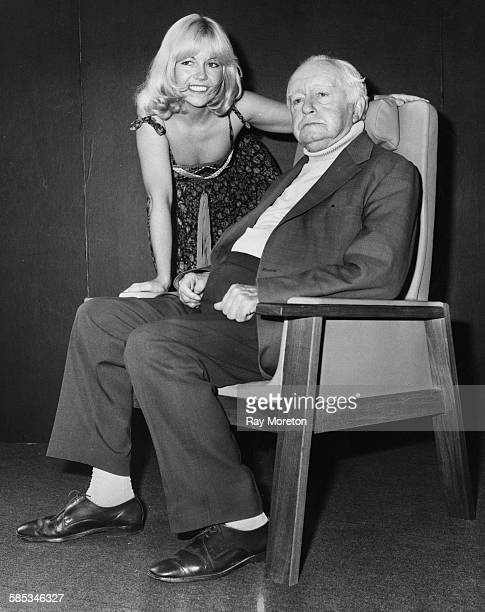 Actor Arnold Ridley well known for playing Private Godfrey in the television show 'Dad's Army' sitting in an armchair next to a young model as he...