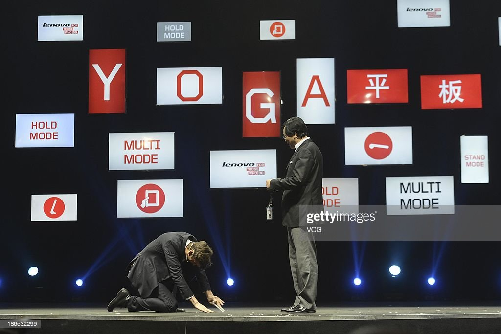 Actor Ashton Kutcher named Lenovo product engineer receives a staff card from Lenovo Chief Executive Officer Yang Yuanqing (R) during the launching ceremony of Yoga Tablet at China National Convention Center on November 1, 2013 in Beijing, China. The world's largest personal computer maker Lenovo launched its high-end product Yoga today.