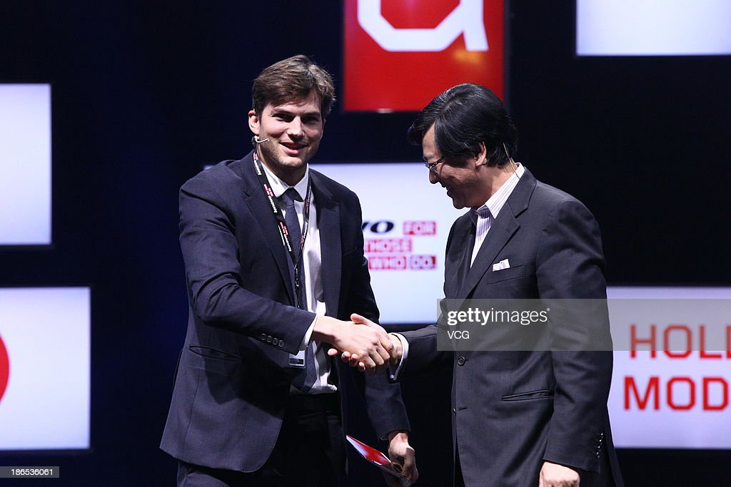 Actor <a gi-track='captionPersonalityLinkClicked' href=/galleries/search?phrase=Ashton+Kutcher&family=editorial&specificpeople=202015 ng-click='$event.stopPropagation()'>Ashton Kutcher</a> named Lenovo product engineer shakes hands with Lenovo Chief Executive Officer <a gi-track='captionPersonalityLinkClicked' href=/galleries/search?phrase=Yang+Yuanqing&family=editorial&specificpeople=2195940 ng-click='$event.stopPropagation()'>Yang Yuanqing</a> (R) during the launching ceremony of Yoga Tablet at China National Convention Center on November 1, 2013 in Beijing, China. The world's largest personal computer maker Lenovo launched its high-end product Yoga today.