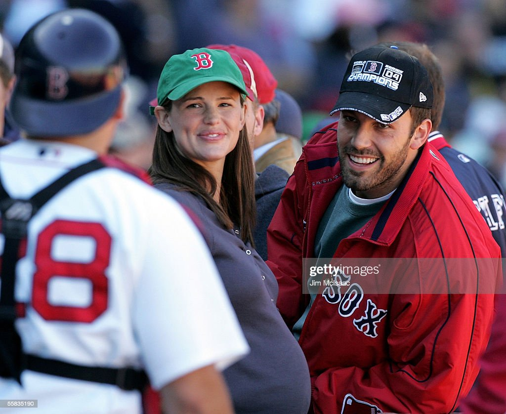 Actor Ben Affleck and wife actress Jennifer Garner smile at catcher Doug Mirabelli of the Boston Red Sox as they attend the game against the New York...
