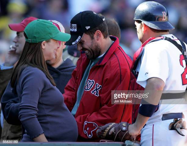 Actor Ben Affleck laughs with his wife actress Jennifer Garner and catcher Doug Mirabelli of the Boston Red Sox as they attend the game against the...