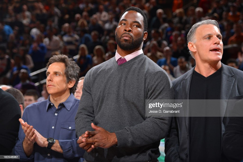 Actor Ben Stiller (L) and Justin Tuck (C) of the New York Giants watch the game between the Philadelphia 76ers and the New York Knicks on February 24, 2013 at Madison Square Garden in New York City, New York.
