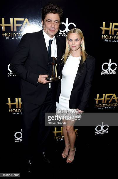 Actor Benicio Del Toro winner of the Hollywood Supporting Actor Award for 'Sicario' poses with actress Reese Witherspoon in the press room during the...