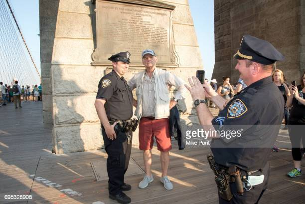 Actor Bill Murray poses for a photo with a NYC police officer during the 22nd Annual Poets House Poetry Walk Across The Brooklyn Bridge on June 12...
