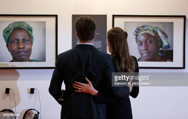 Actor Brad Pitt and UN Special Envoy and actress Angelina Jolie view photographs of victims of violence as they attend the Global Summit to End...