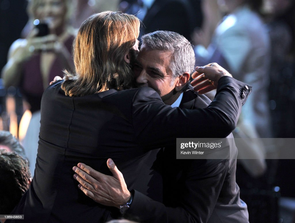 Actor Brad Pitt gives actor George Clooney a congratulatory hug as he walks onstage to accept the Best Actor award for 'The Descendants' during the 17th Annual Critics' Choice Movie Awards held at The Hollywood Palladium on January 12, 2012 in Los Angeles, California.