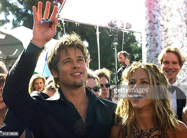 Actor Brad Pitt waves to spectators as he arrives with his girlfriend actress Jennifer Aniston at the Shrine Auditorium in Los Angeles CA 12...
