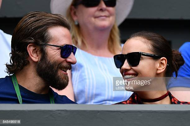 US actor Bradley Cooper and Russian model Irina Shayk sit in centre court before the men's semifinal match on the tweflth day of the 2016 Wimbledon...