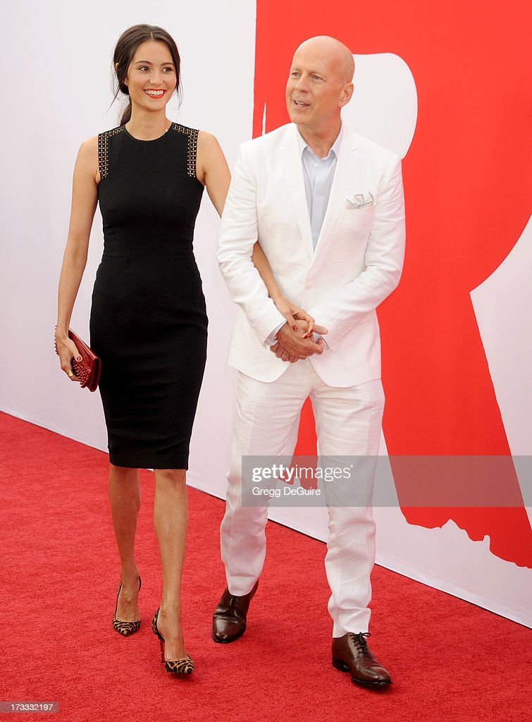 Actor Bruce Willis and Emma Heming arrive at the Los Angeles premiere of 'Red 2' at Westwood Village on July 11, 2013 in Los Angeles, California.
