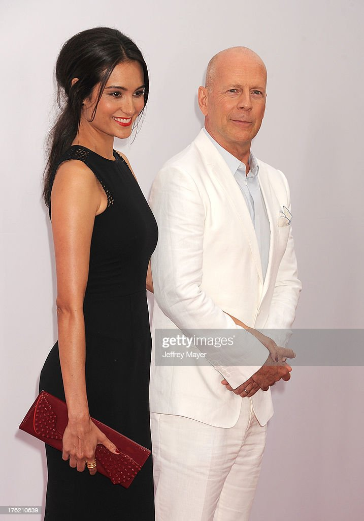 Actor Bruce Willis (R) and Emma Heming arrive at the 'RED 2' - Los Angeles Premiere at Westwood Village on July 11, 2013 in Los Angeles, California.