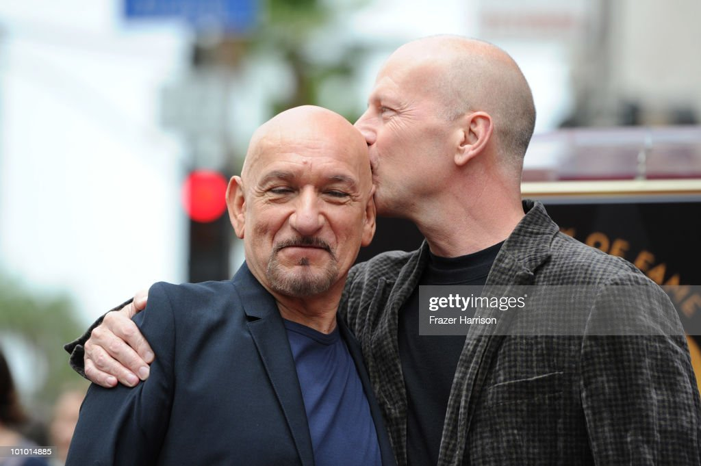 Actor Bruce Willis (right) kisses actor Sir Ben Kingsley who was honored with the 2,410th Star on the Hollywood Walk of Fame on May 27, 2010 in Hollywood, California.
