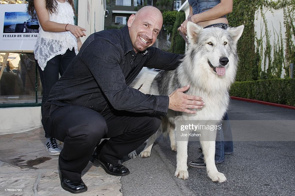 Actor Bruno Amato poses for a photo with Ranger a wolf from the Wolfconnection.org at Richard Grieco's opening night gala for his one-man art exhibit 'Sanctum Of A Dreamer!' at Gallerie Sparta on August 15, 2013 in West Hollywood, California.