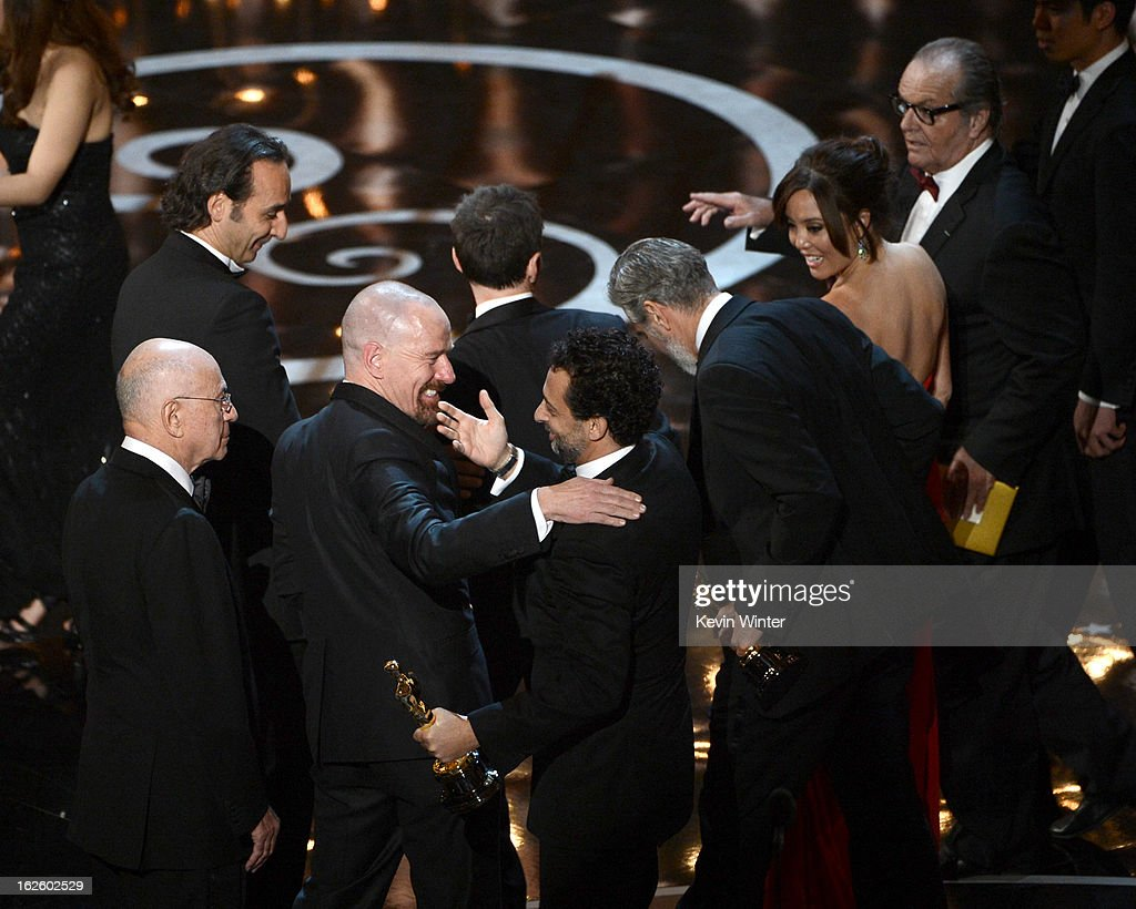 """Actor Bryan Cranston hugs producer Grant Heslov after they accept the Best Picture award for """"Argo"""" onstage during the Oscars held at the Dolby Theatre on February 24, 2013 in Hollywood, California."""