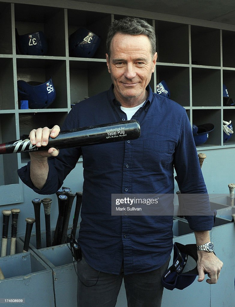 Actor Bryan Cranston poses in the Dodger dugout with a Yasiel Puig bat before the MLB game between the Cincinnatti Reds and Los Angeles Dodgers at Dodger Stadium at Dodger Stadium on July 26, 2013 in Los Angeles, California.