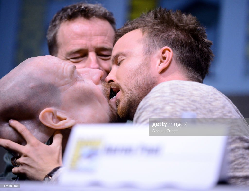 Actor <a gi-track='captionPersonalityLinkClicked' href=/galleries/search?phrase=Bryan+Cranston&family=editorial&specificpeople=217768 ng-click='$event.stopPropagation()'>Bryan Cranston</a> watches actor <a gi-track='captionPersonalityLinkClicked' href=/galleries/search?phrase=Aaron+Paul+-+Actor&family=editorial&specificpeople=693211 ng-click='$event.stopPropagation()'>Aaron Paul</a> kiss a Walter White face mask onstage at the 'Breaking Bad' panel during Comic-Con International 2013 at San Diego Convention Center on July 21, 2013 in San Diego, California.