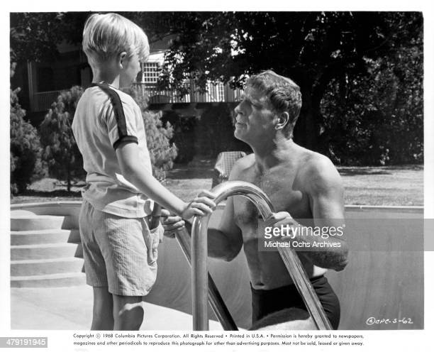 Actor Burt Lancaster talks to a little boy in a scene of the Columbia Pictures movie 'The Swimmer' circa 1968