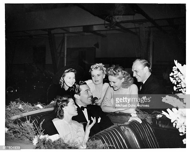 Actor Cesar Romero talks with Betty Grable as Jackie Coogan and Marie Wilson look on in Los Angeles California