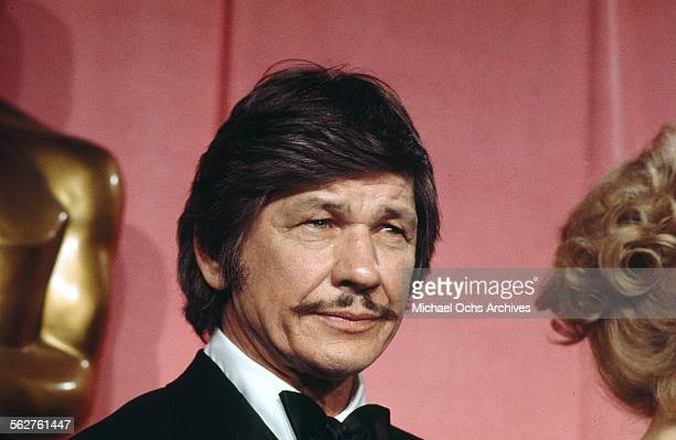 Actor Charles Bronson poses backstage after presenting 'Best Supporting Actress' award during the 46th Academy Awards at Dorothy Chandler Pavilion in...