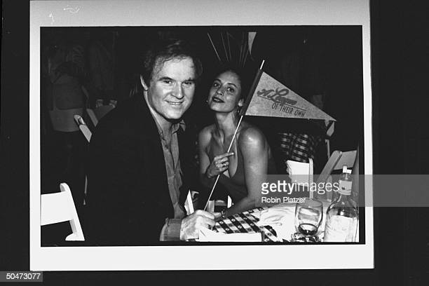 Actor Charles Grodin sitting at table w actress Sonia Braga who is holding a pennant flag for the movie A League of Their Own during premiere party...