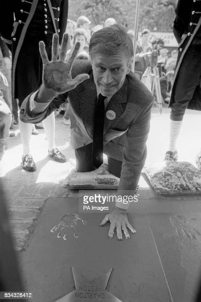 Actor Charlton Heston leaving a handprint impression in Leicester Square also leaving a mark were Sir John Mills Dame Anna Neagle and Omar Sharif
