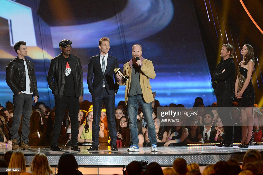 Actor Chris Evans, actor Samuel L. Jackson, actor Tim Hiddleston and filmmaker Joss Whedon speak as actor Brad Pitt and stands nearby onstage during the 2013 MTV Movie Awards at Sony Pictures Studios on April 14, 2013 in Culver City, California.