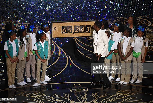 Actor Chris Rock prent the amount of money collected by the Girl Scouts on stage at the 88th Oscars on February 28 2016 in Hollywood California AFP...