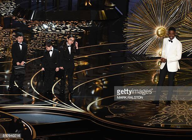 Actor Chris Rock presents children representing accountants from PricewaterhouseCoopers on stage at the 88th Oscars on February 28 2016 in Hollywood...