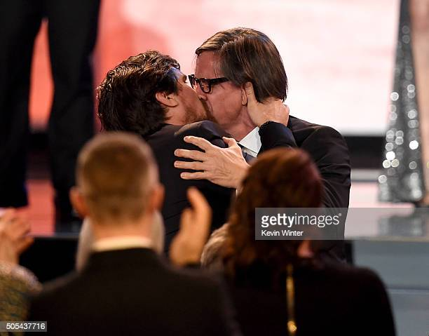 Actor Christian Bale and screenwriter Charles Randolph kiss onstage as they accept the Best Comedy award for 'The Big Short' during the 21st Annual...