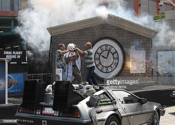 Actor Christopher Lloyd and writer Bob Gale who wrote and cocreated the film 'Back to the Future' participate with an actor playing the character of...