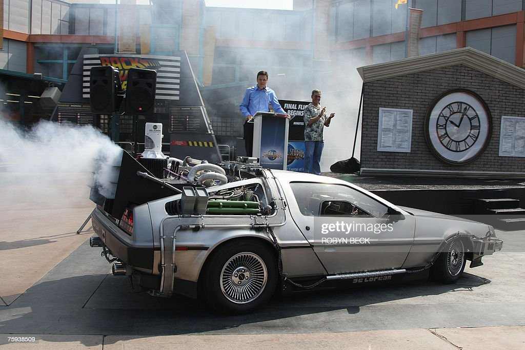 Actor Christopher Lloyd (in passenger seat) arrives in a DeLorean car at Universal Studios Hollywood's 'Back to the Future - The Ride' in University City, California, 02 August 2007. Lloyd, who portrayed Doc Brown in the 1985 film 'Back to the Future,' made the apearence to mark a month-long countdown to the closure of the 14-year-old ride. The DeLorean Motor Co. (Texas), a suburban Houston company that rebuilds DeLoreans, recently announced plans to manufacture a limited number of new Deloreans in 2008. The last DeLorean rolled off the assembly line in Northern Ireland in 1982. On the podium are 'Back to the Future' writer and co-creator Bob Gale (R) and Universal Studios Hollywood's Chris MacKenzie (L).