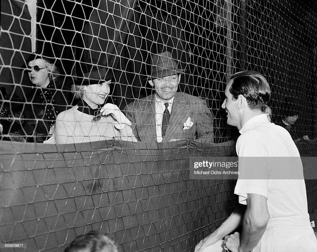 Actor Clark Gable and wife actress Carole Lombard talk with Bill Tildon during an event in Los Angeles, California.