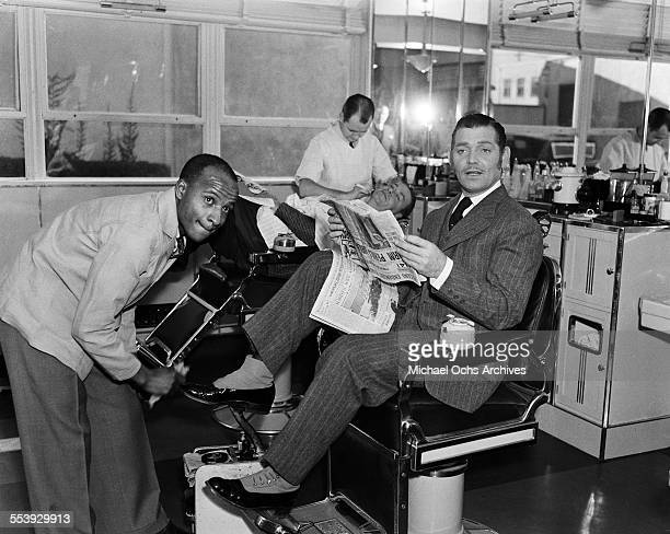 Actor Clark Gable poses in costume for the MGM film 'Parnell' as he gets his shoes shined in Los Angeles California