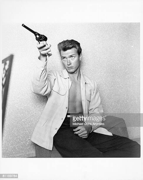 Actor Clint Eastwood checks his gun at home on June 1 1956 in Los Angeles California