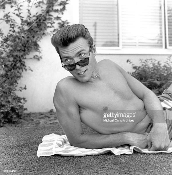 Actor Clint Eastwood lies on a towel and looks over his sunglasses at home on June 1 1956 in Los Angeles California