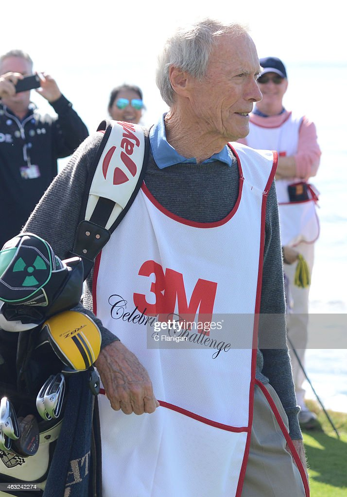 Actor Clint Eastwood switches roles with his caddie for the day Nick Faldo on the 18th tee during the 3M Celebrity Challenge before the AT&T Pebble Beach National Pro-Am at the Pebble Beach Golf Links on February 11, 2015 in Pebble Beach, California.