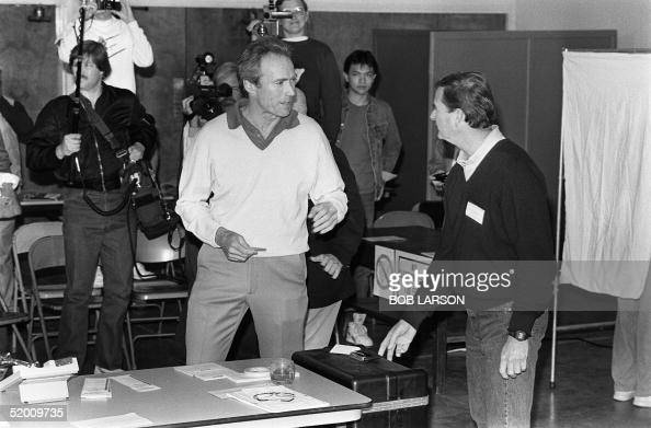 US actor Clint Eastwood with a signed ballot in his hand has a few words with Dan Muster on his way to dropping his ballot in the box 08 April 1986...