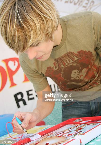 Actor Cody Linley plays the game 'Operation' at the Operation Rescue Kit game Mobile Rescue Unit booth at the State Fair of Texas at Fair Park on...