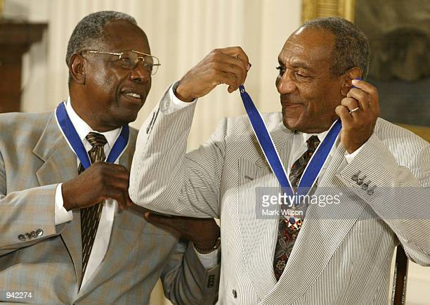 Actor Comedian Bill Cosby jokes with baseball great Hank Aaron after they both received the Presidential Medal of Freedom Award from US President...