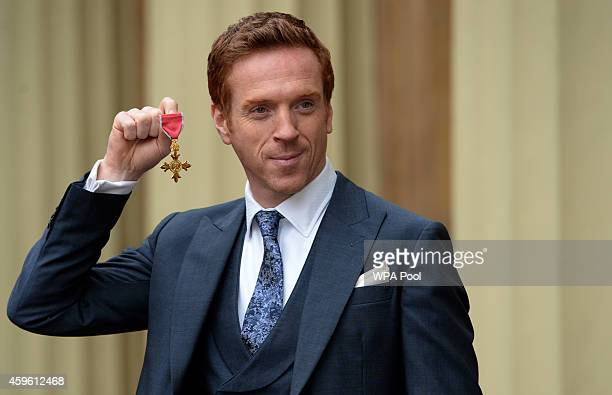 Actor Damian Lewis holds his Officer of the Order of the British Empire after the Investiture ceremony at Buckingham Palace on November 26 2014...