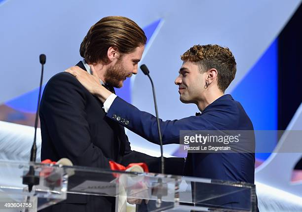 Actor Daniel Bruhl presents The Jury Prize to director Xavier Dolan for his film 'Mommy' during the Closing Ceremony at the 67th Annual Cannes Film...