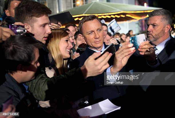 Actor Daniel Craig takes a selfie with fans as he attends the German premiere of the new James Bond movie 'Spectre' at CineStar on October 28 2015 in...