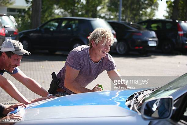 Actor Daniel Roesner pushes a car during the photocall for the action series 'Alarm Fuer Cobra 11' on August 31 2015 in Cologne Germany