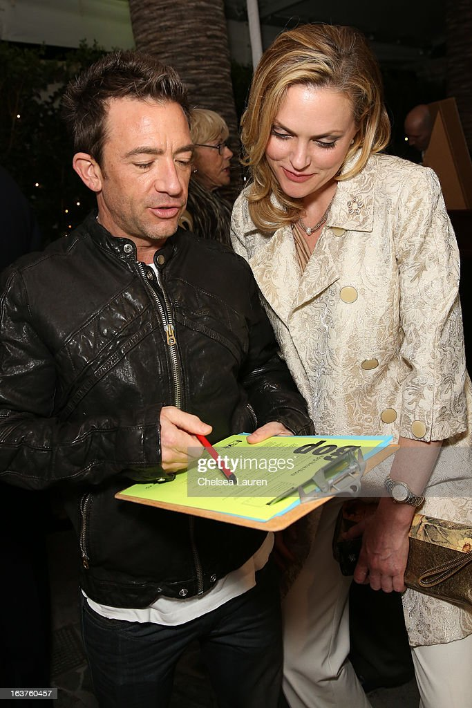 Actor David Faustino fills out puppy adoption paperwork (L) while speaking to actress Elaine Hendrix at Much Love Animal Rescue's makeovers for mutts at Peninsula Hotel on March 14, 2013 in Beverly Hills, California.