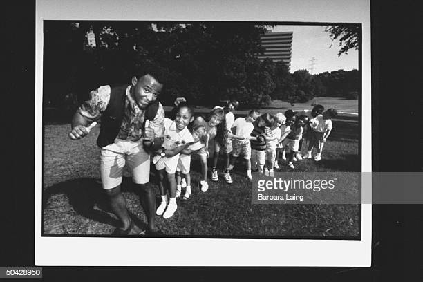 Actor David Joyner who plays Barney the lovable purple dinosaur on the PBS program Barney Friends marching in front of a train of boys and girls in...